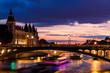 Night view of Conciergerie Castle and Pont Notre-Dame bridge over river Seine. Paris, France