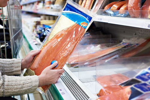 Fototapeta Woman buys lightly salted red fish in store