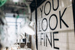 Black lettering 'You Look Fine' on white wall'