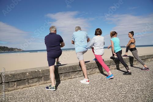 Grupa starsi ludzie rozciąga plażą z powierniczą dziewczyną