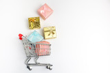 Colorful gifts box, supermarket shopping cart on white wooden background