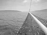 Kroatische Inseln im Meer mit Bug eines Segelschiffs im Vordergrund in schwarzweiß
