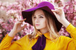 Outdoor close up portrait of young beautiful fashionable girl posing in street with blooming trees, wearing stylish wide-brimmed violet hat, yellow shirt, bow tie. Female spring fashion concept