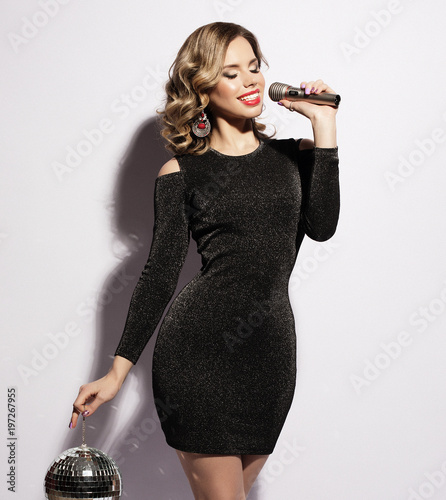 lifestyle and people concept: Young woman wearing black dress, holding disco ball  and  singing into microphone - 197267955