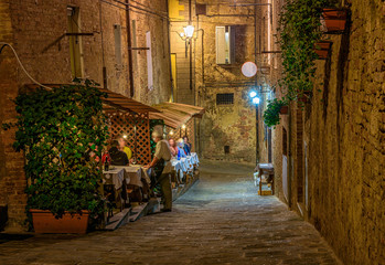 Medieval narrow cozy street with tables of restaurant in Siena, Tuscany, Italy