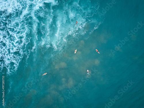 Fototapeta Surfers swim to big wave