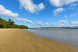 A deserted stretch of beach on a bright day under blue cloudy skies - 197312537