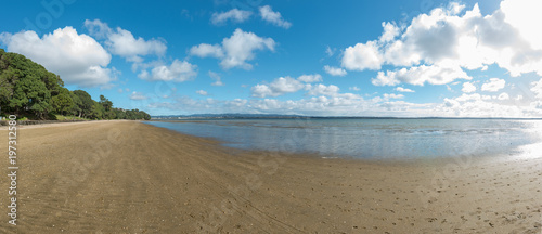 A deserted stretch of beach on a bright day under blue cloudy skies - 197312580
