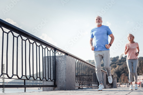Follow me. Confident unshaken athletic man spending time on fresh air looking straight and running across the quay with a woman.