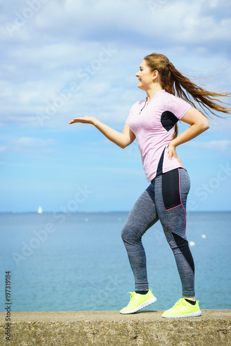 Fototapeta Woman exercising next to sea