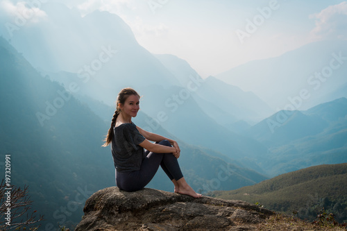 Woman sits on mountain cliff