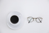 Cup of fresh black espresso coffee with a pair of eyeglasses or spectacles on white viewed from above - 197324981