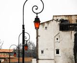Vintage streetlights with orange color glass on the street in Arles (Provence, France). Concepts of unique, different and standing out. Toned photo.