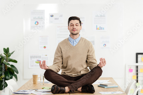 relaxed businessman with eyes closed sitting in lotus position on table in office