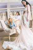 Young smiling bride and bridesmaids with dresses in wedding fashion shop - 197328700