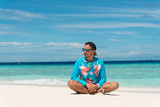 Man sit on sandy beach with transparent water of ocean in Maldives - 197331349