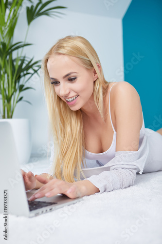 Smiling woman using a laptop while lying