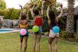 Friends playing balloon bursting game at party - 197335100