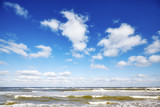 Blue sky with clouds over a sea