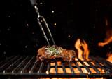 Fiery grill grid with piece of beef steak.