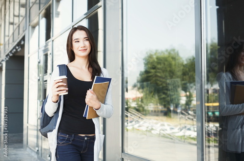 Beautiful student girl with textbooks and coffee