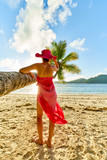 Woman tourist with sarong under coconut palm tree, seychelles