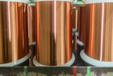 Standard copper wire enamel in a bobbin on the table, steel floor in the factory. The backdrop is a machine. Winding machine - 197367521