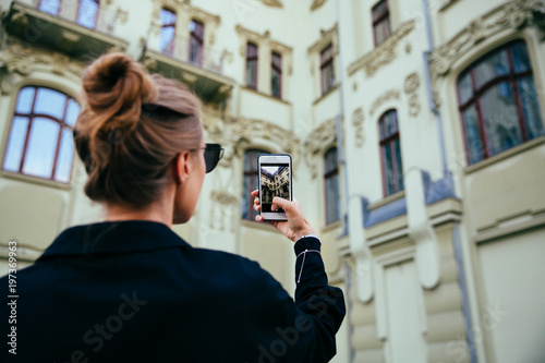 Young woman takes a photo of architecture on smartphone