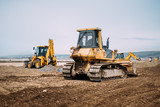 Industrial motor grader and backhoe excavator on highway construction site - 197372123