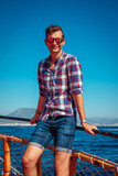 Young man enjoys the seaside view on a wooden yacht - 197384195