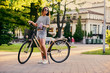 An attractive brunette female with a bicycle in the city park.