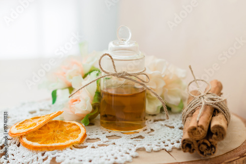 Made at home from orange oil with cinnamon perfume in a glass jar. Slices of dried orange, dried cinnamon and flowers. Crocheted white napkin. Perfumer.Natural and healthy cosmetic. Wooden background.