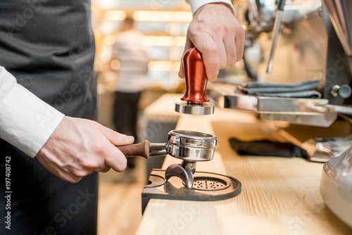 Pressing a coffee with temper into the handle of the professional coffee machine