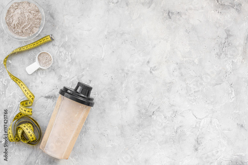 sport nutrition set with protein powder for cocktail and measure tape gray stone background top view space for text