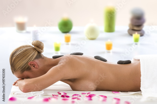 Hot stone massage rocks. Spa stones of woman in spa salon. woman on candles background has therapy and skincare in luxary spa salon. © JPC-PROD