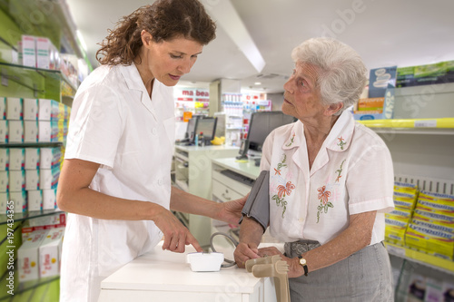 Young smiling female pharmaceutist taking old woman disabled,with crutches, blood pressure using sphygmomanometer in a real pharmacy backgroud