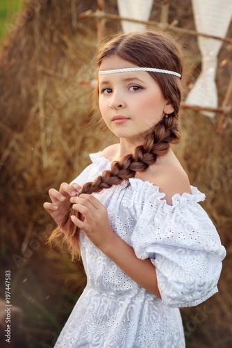 Девочка с косой в белом платье летом в поле стоит у стога сена