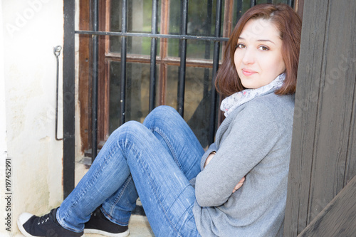 beautiful young woman sitting on the edge of the window of the house outside