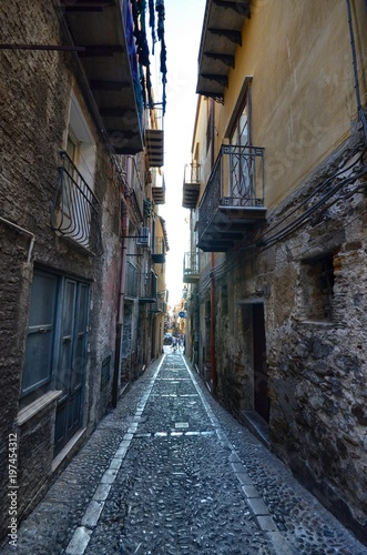 Fotobehang Smalle straatjes Cefalù, Italy, Sicily August 16 2015. The alleys of cefalù that wind at the foot of the fortress behind the cathedral. Steep stairways, picturesque signs. Narrow streets, flower boxes, laundry threads