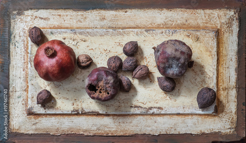 Dried pomegranates and walnutes on a wooden background, - 197461740