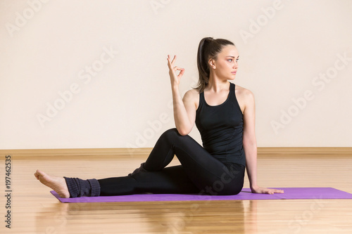 Young woman is practicing yoga in half lord of the fishes pose at gym.