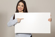 Happy woman showing empty blank paper card sign with copy space for text