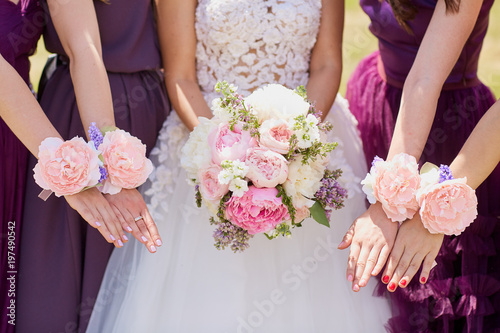 Hands of the bride and girlfriend with decorative flowers in the open air.