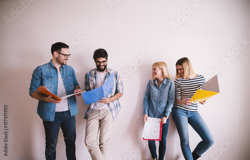 Two groups of young men and women leaning against the wall having fun before a job interview with folders in hands in the waiting room.
