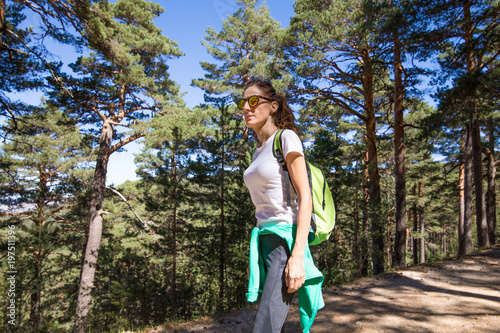 side view of sport hiker woman with white shirt grey trousers walking or trekking on a forest path in Navacerrada mountain, in Guadarrama Natural Park, Madrid, Spain