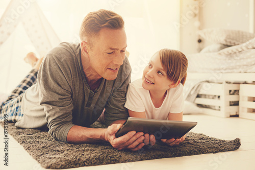 Family time. Joyful positive delighted father and daughter lying on the floor and using a tablet while spending time together