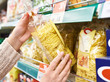 Pack of pasta in hands of buyer at store - 197523769