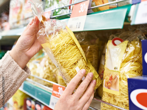 Pack of pasta in hands of buyer at store