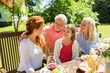 leisure, holidays and people concept - happy female family having festive dinner at summer garden and talking