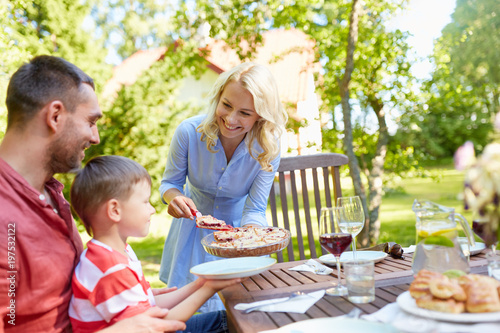 leisure, family and people concept - happy mother, father and little son eating pie at festive dinner or summer garden party - 197532122